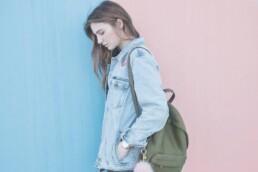 Tricks gegen Angst und Depression in der Corona Pandemie - Nachdenkliche junge Frau vor zweifarbiger Wand