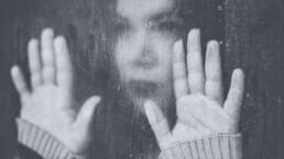 Wie körperlicher und psychischer Missbrauch mein Leben zeichnete - Frau hinter Fenster