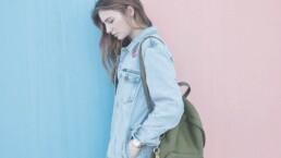 Wie ich einfach lernte mein Leben zu lieben und meine Krankheit zu akzeptieren - Junge Frau vor zweifarbiger Wand